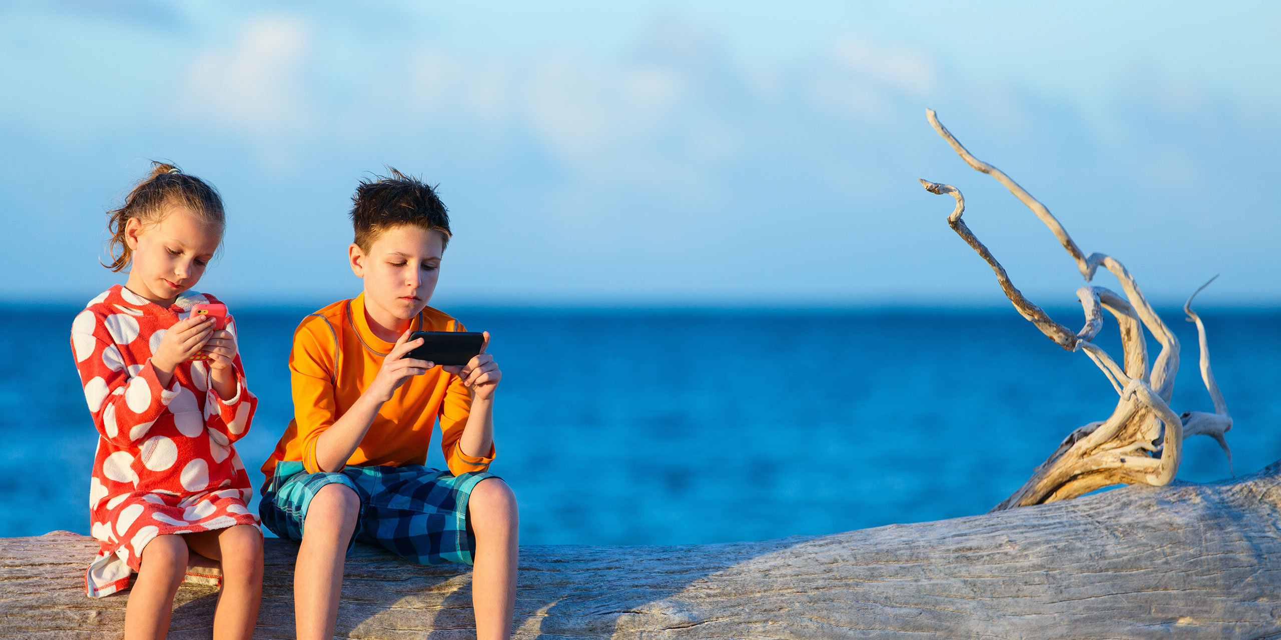 Kids on Smartphones on Beach; Courtesy of BlueOrange Studio/Shutterstock.com