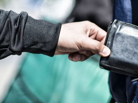 Thieve pickpocketing wallet; Courtesy of DDekk/Shutterstock.com