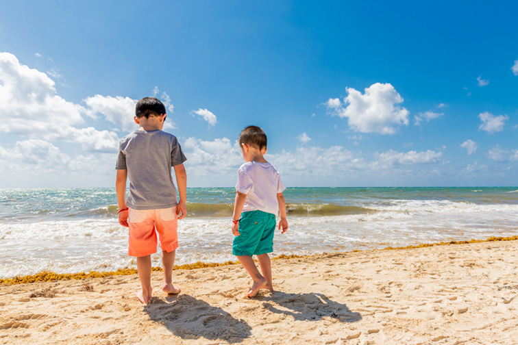 Brothers at the beach during sunny vacation in Cancun, Mexico ; Courtesy of CS W/Shutterstock