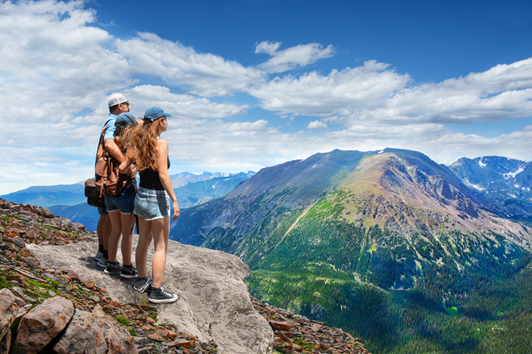 family on hiking trip, on top of mountain rock. View from Trail Ridge Road.Rocky Mountains National Park, Colorado ; Courtesy of margaret.wiktor/Shutterstock