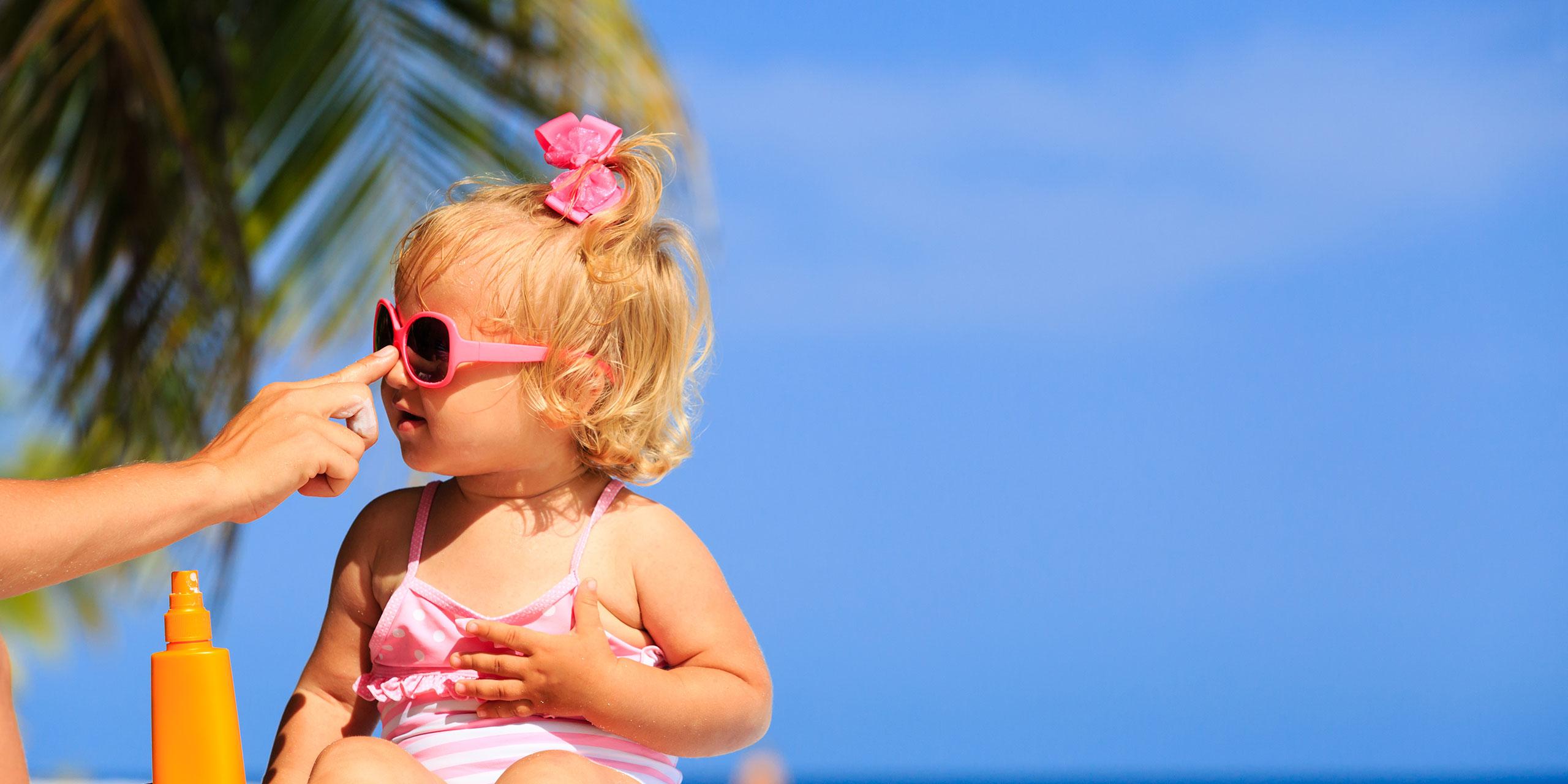Baby Getting Sunscreen Applied; Courtesy of NadyaEugene/Shutterstock.com