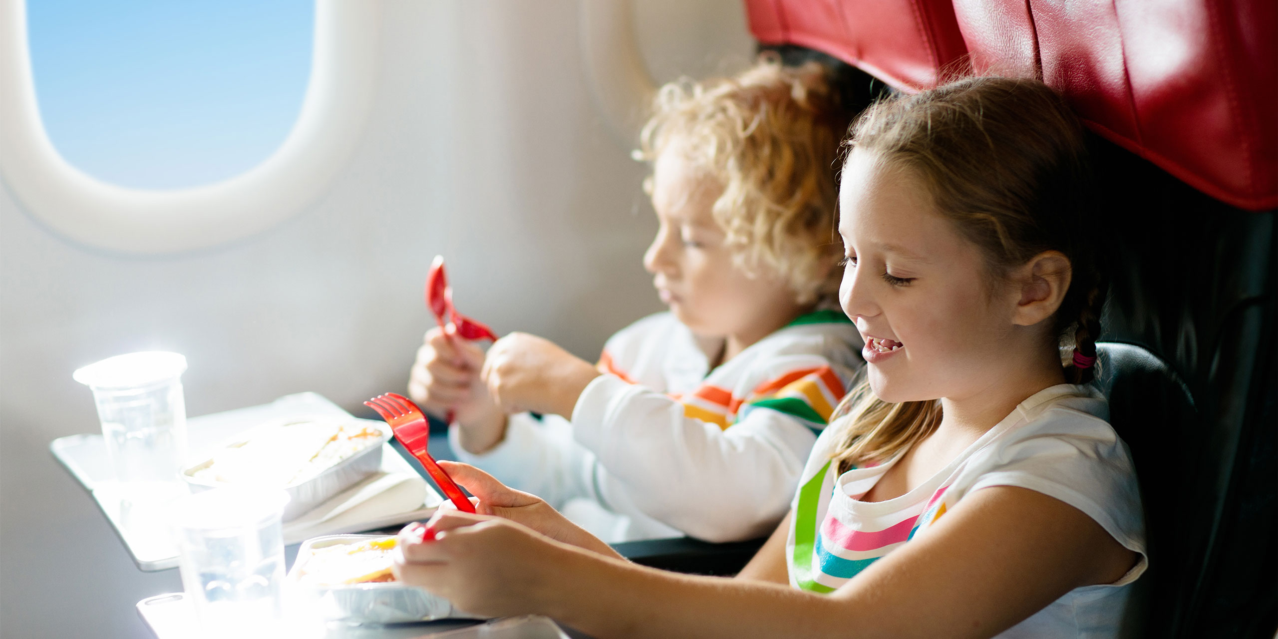 Kids Eating Snacks On A Plane; Courtesy of FamVeld/Shutterstock.com