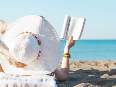 Woman Reading on the Beach; Courtesy of Ahmet Misirligul/Shutterstock.com