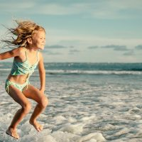 Little Girl Jumping in Ocean; Courtesy of altanaka/Shutterstock.com