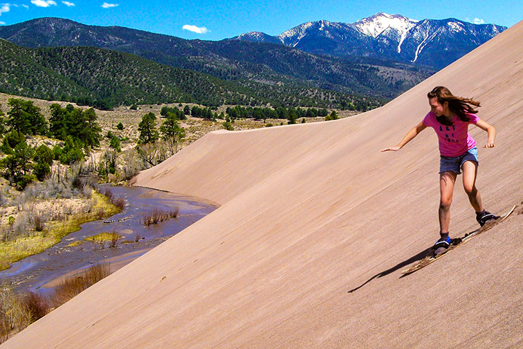 Great Sand Dunes National Park Girl Sandboarding Above Medano Creek, Castle Creek Picnic Area; Courtesy NPS