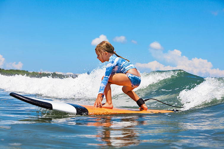 Young Girl Surfs in Maui
