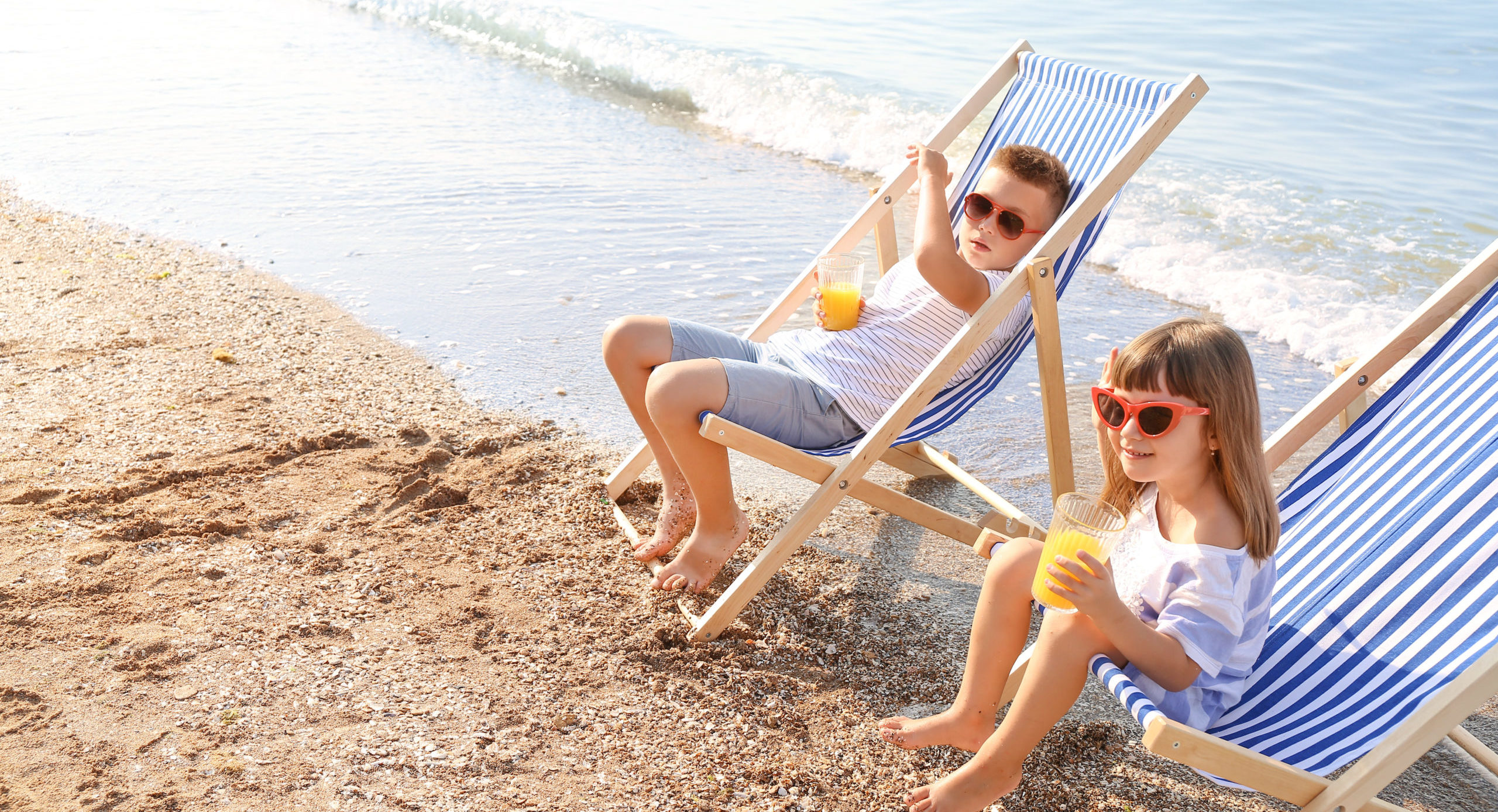 Two children drinking juice on the beach in beach chairs