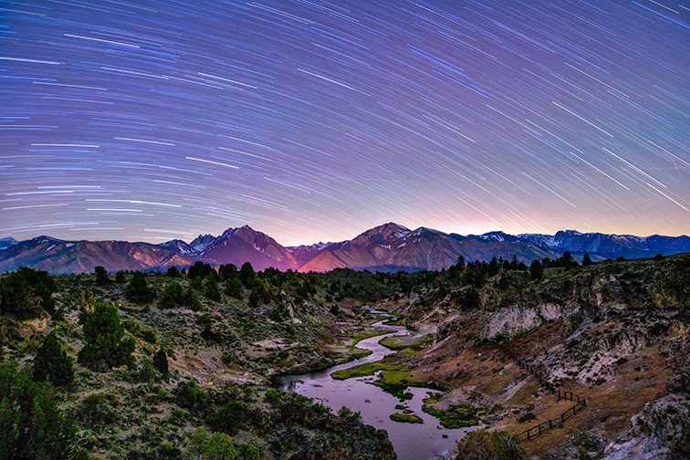 Star Trails over Hot Creek geothermal area at night with the Eastern Sierra mountains in the background, Mammoth Lakes, California; Courtesy of Bill45/Shutterstock