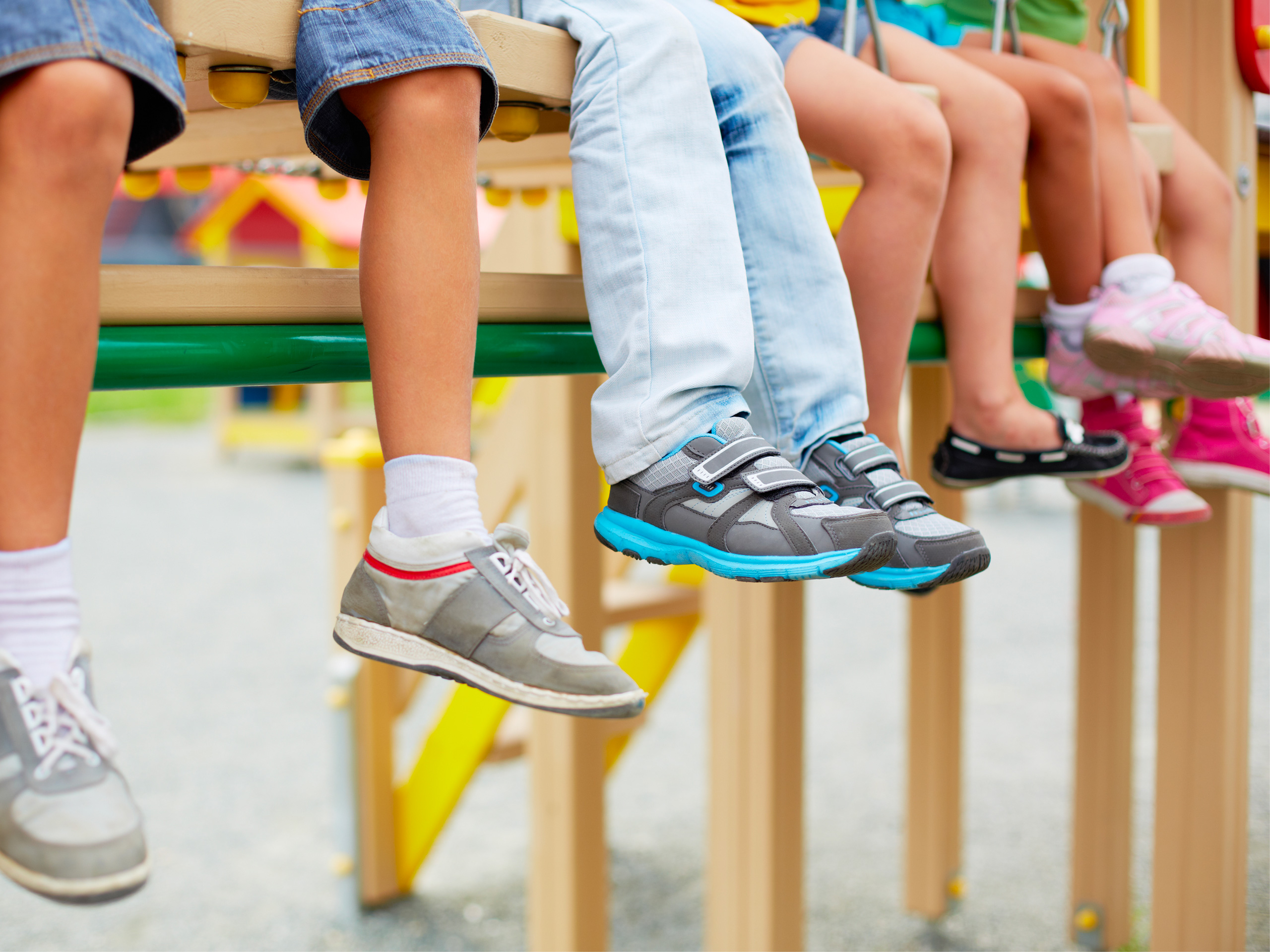 kids sitting in a row with sneakers