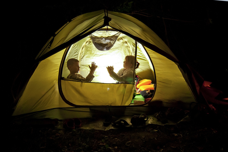 children play in the hike. the tent lights at night from the flashlight. dark silhouettes of children. Courtesy of Ivan Kovbasniuk/Shutterstock