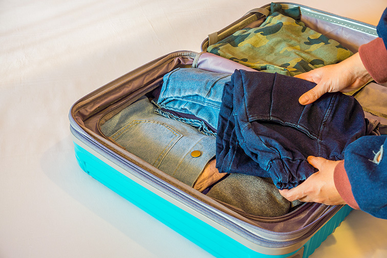 clothes folded in suitcase: Courtesy of JoeyPhoto/Shutterstock