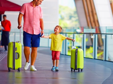 father and son with luggage airport