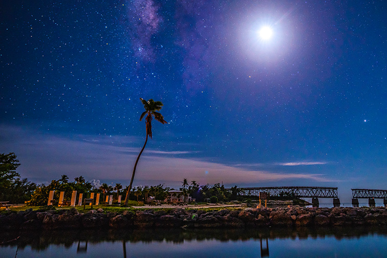 bahia honda state park broken bridge florida keys at night with a moon and milky way stars and palm tree; Courtesy of travelphotoguy/Shutterstock