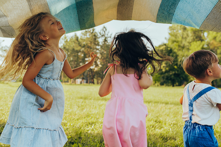 layful children playing under the blanket, jumping and dancing together. ; Courtesy of Yuricazac/Shutterstock