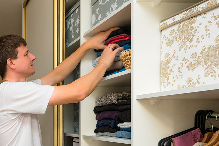 man sorts through clothes closet; Courtesy of AlesiaKan/Shutterstock