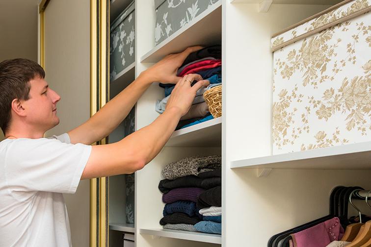 man sorts through clothes closet; Courtesy of AlesiaKan/Shutterstock
