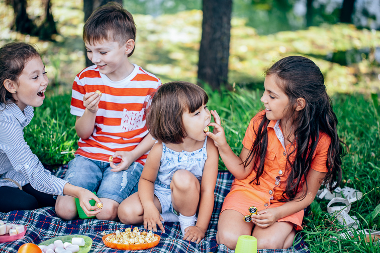 group of kids sitting on a picnic in the woods in the evening rays of sunlight are feed each other; Courtesy of UfaBizPhoto/Shutterstock