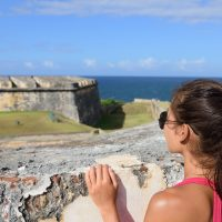 Puerto Rico travel tourist woman in San Juan, looking down at the fort Castillo San Felipe Del Morro; Courtesy of Maridav/Shutterstock