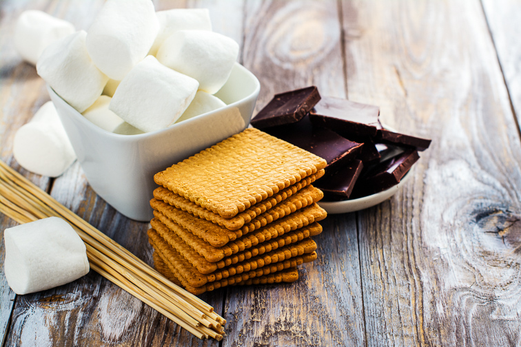 Smores dessert ingredients on wooden table. Picnic or camp concept. Courtesy of Ekaterina Markelova/Shutterstock