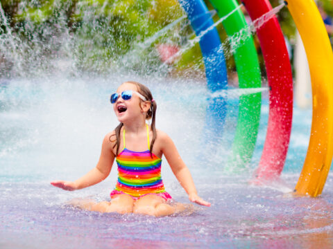 Kids play in aqua park. Children at water playground of tropical amusement park. Little girl at swimming pool. Child playing at water slide on summer vacation in Asia. Courtesy of Famveld/Shutterstock