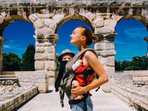 mother with baby child in carrier in the old town of Pula, Croatia; Courtesy of Natalia Deriabina/Shutterstock