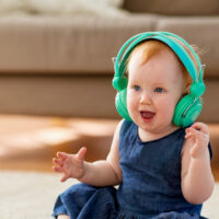 lovely redhead baby girl in headphones listening to music at home; Courtesy of Syda Productions/Shutterstock