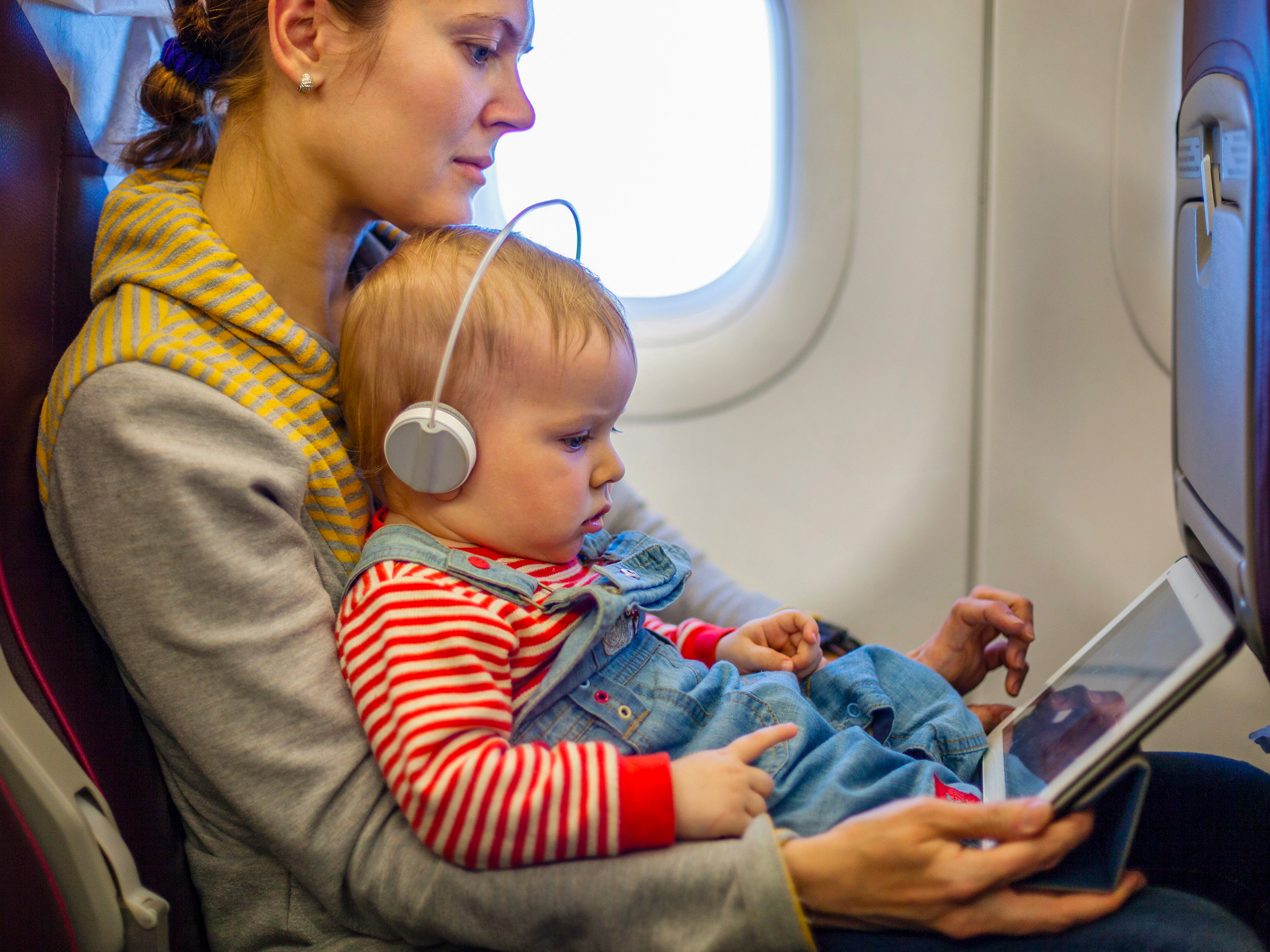 mother and toddler son using tablet pc while on board of airplane; Courtesy of Photobac/Shutterstock
