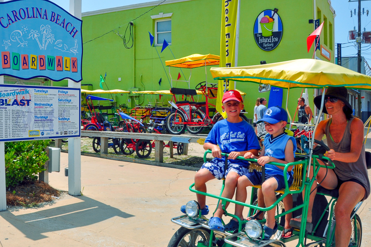 Family renting bikes at carolina beach boardwalk; Courtesy of Wilmington and Beaches CVB