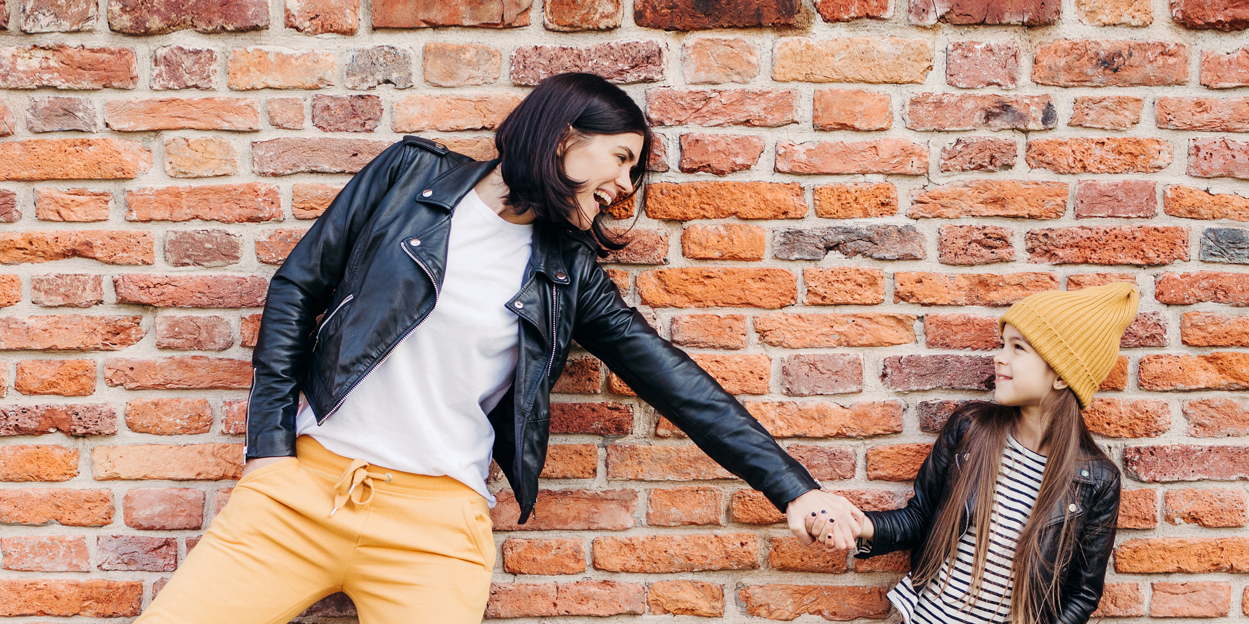 girl and her mother have fun together, keep hands together, pose against brick wall. ; Courtesy of VK Studio/Shutterstock