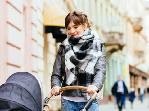 \Young beautiful mother walking with baby carriage in european city center.; Courtesy of Iryna Inshyna/Shutterstock