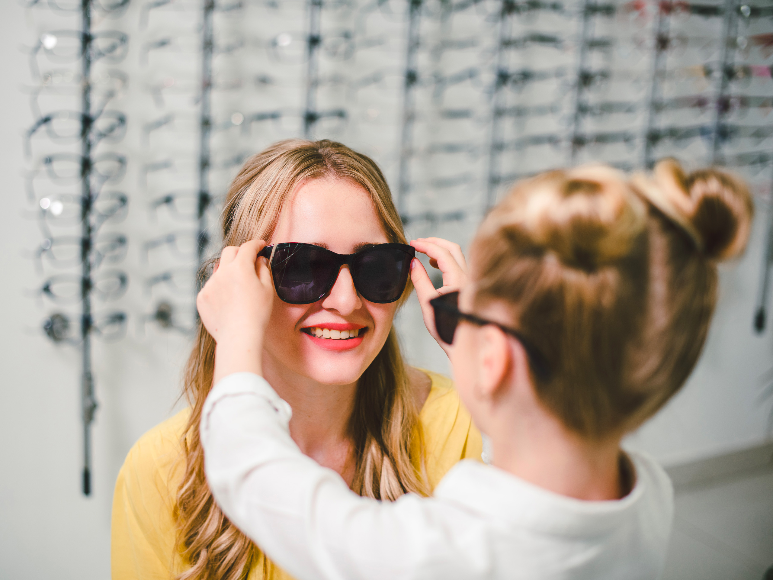 Blonde mom and daughter try the sunglasses in the boutique; Courtesy of Koshevskyi/Shutterstock