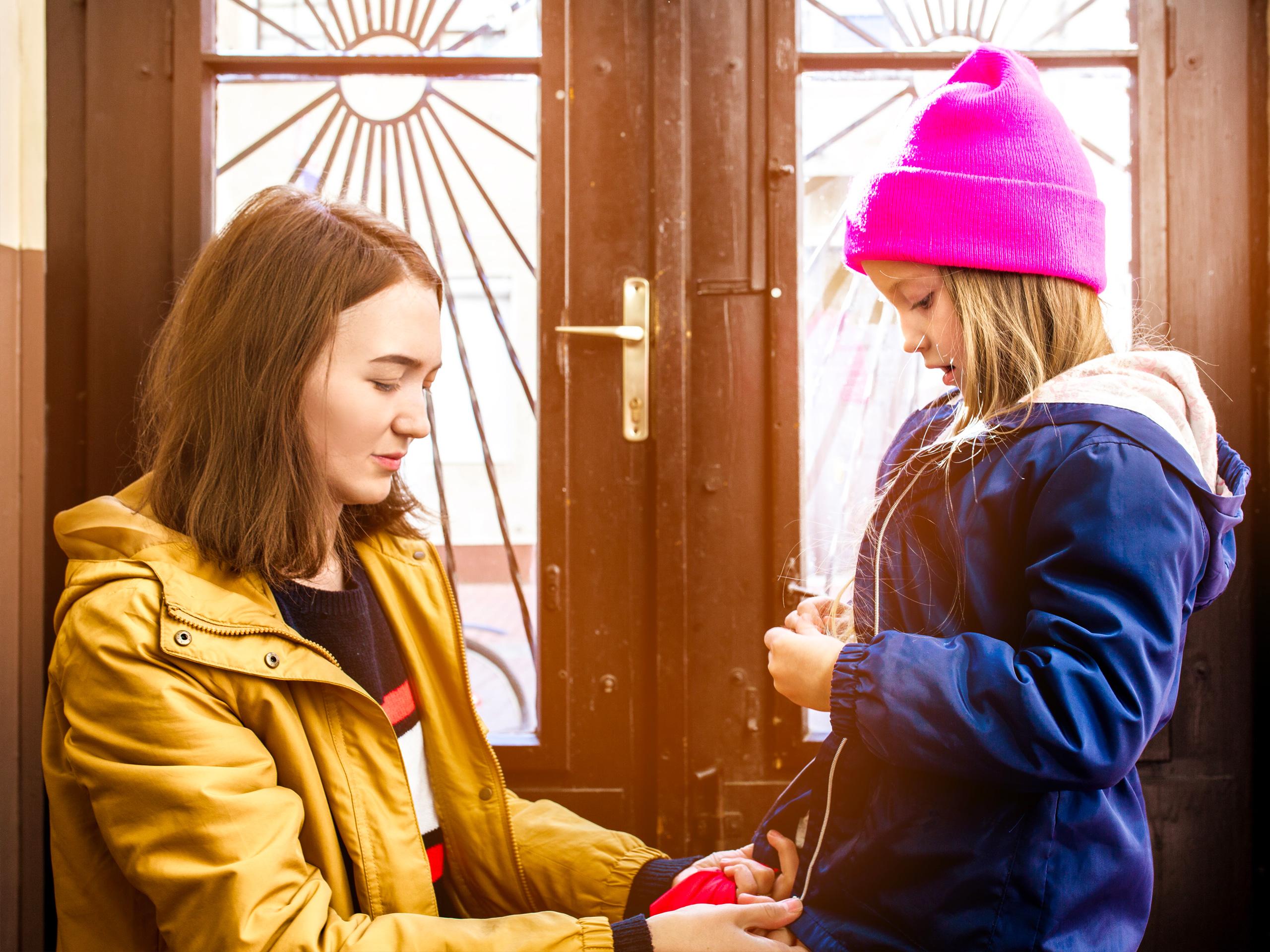 young mother helps her daughter to fasten her jacket next to the front door