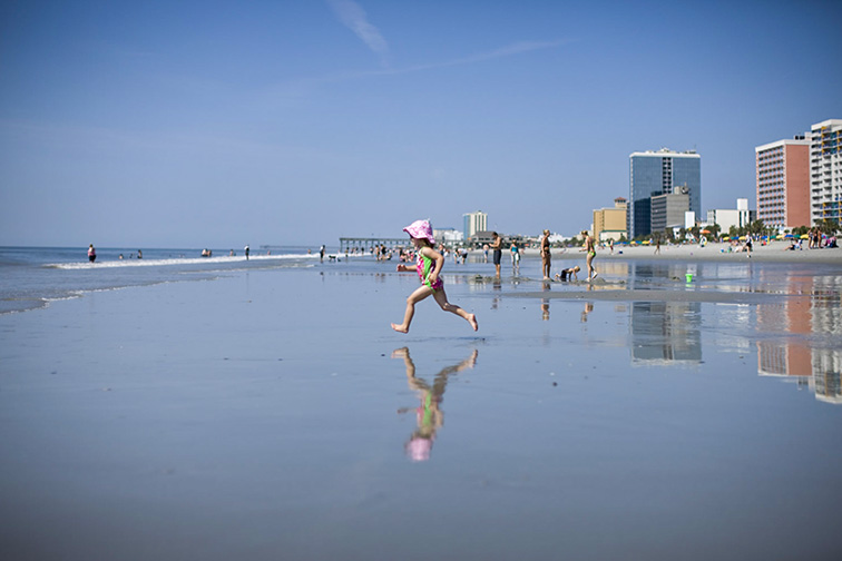 Girl running into the waves; Courtesy of MBACVB