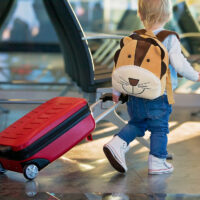 toddler wheeling luggage at airport.; Courtesy of Tomsickova Tatyana/Shutterstock