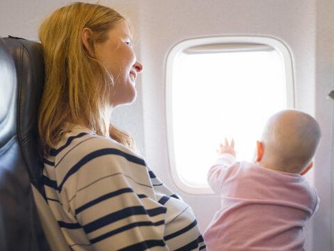 baby on moms lap in flight; Courtesy of Kaspars Grinvalds / Shutterstock