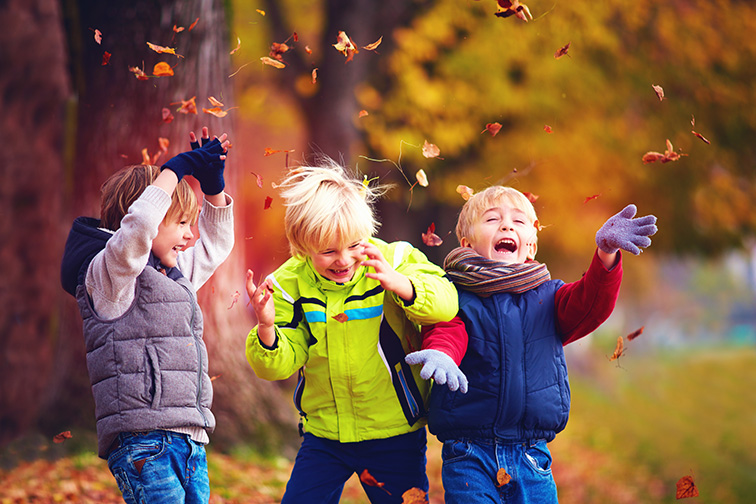 happy friends, schoolchildren having fun in autumn park among fallen leaves; Courtesy of Olesia Bilkei /Shutterstock