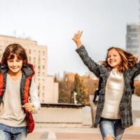 two kids running wearing fall jackets; Courtesy of By YAKOBCHUK VIACHESLAV/Shutterstock