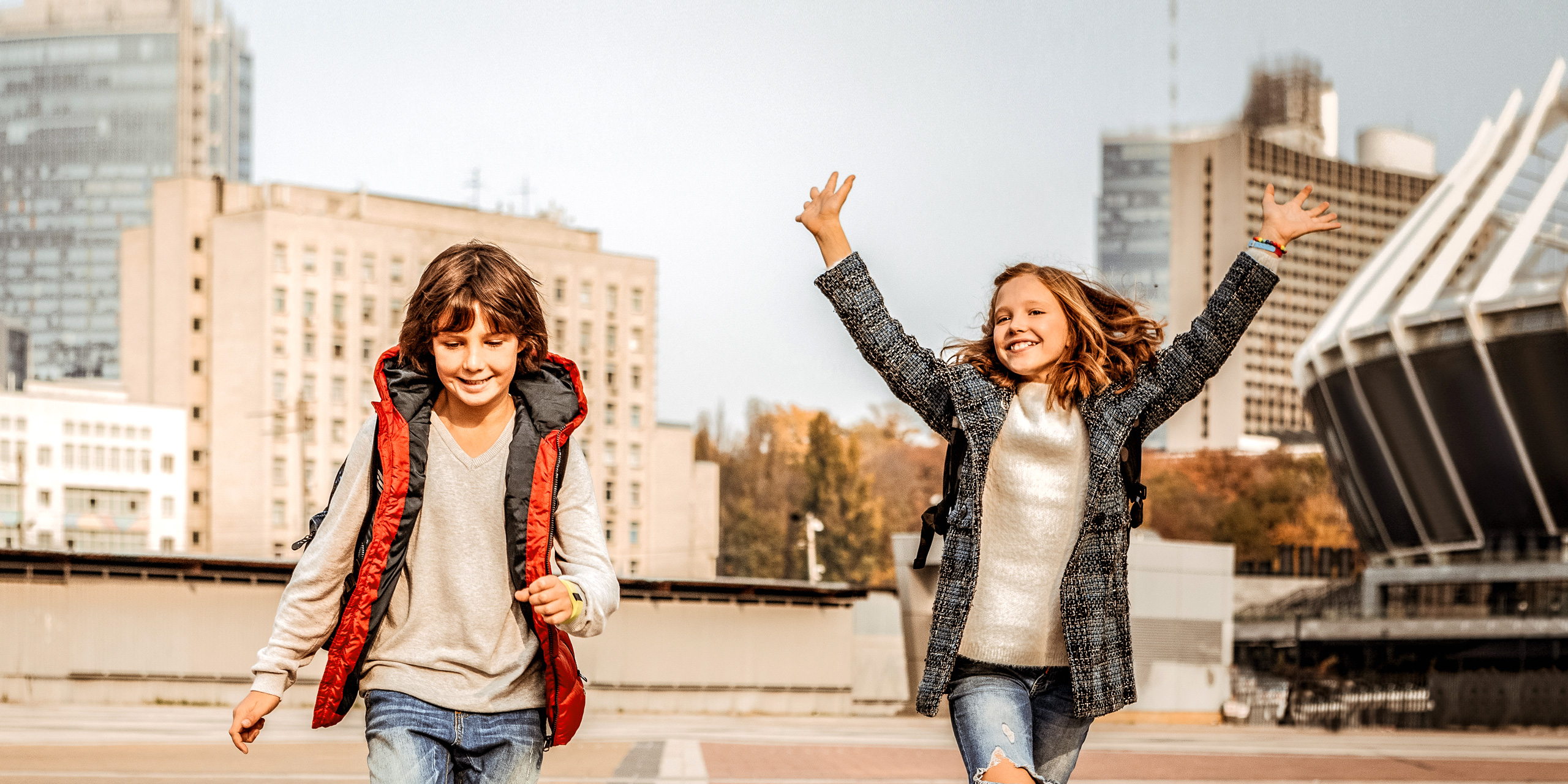 two kids running wearing fall jackets; Courtesy of By YAKOBCHUK VIACHESLAV/Shutterstock