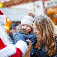 toddler mom christmas market santa; Courtesy of Romrodphoto /Shutterstock