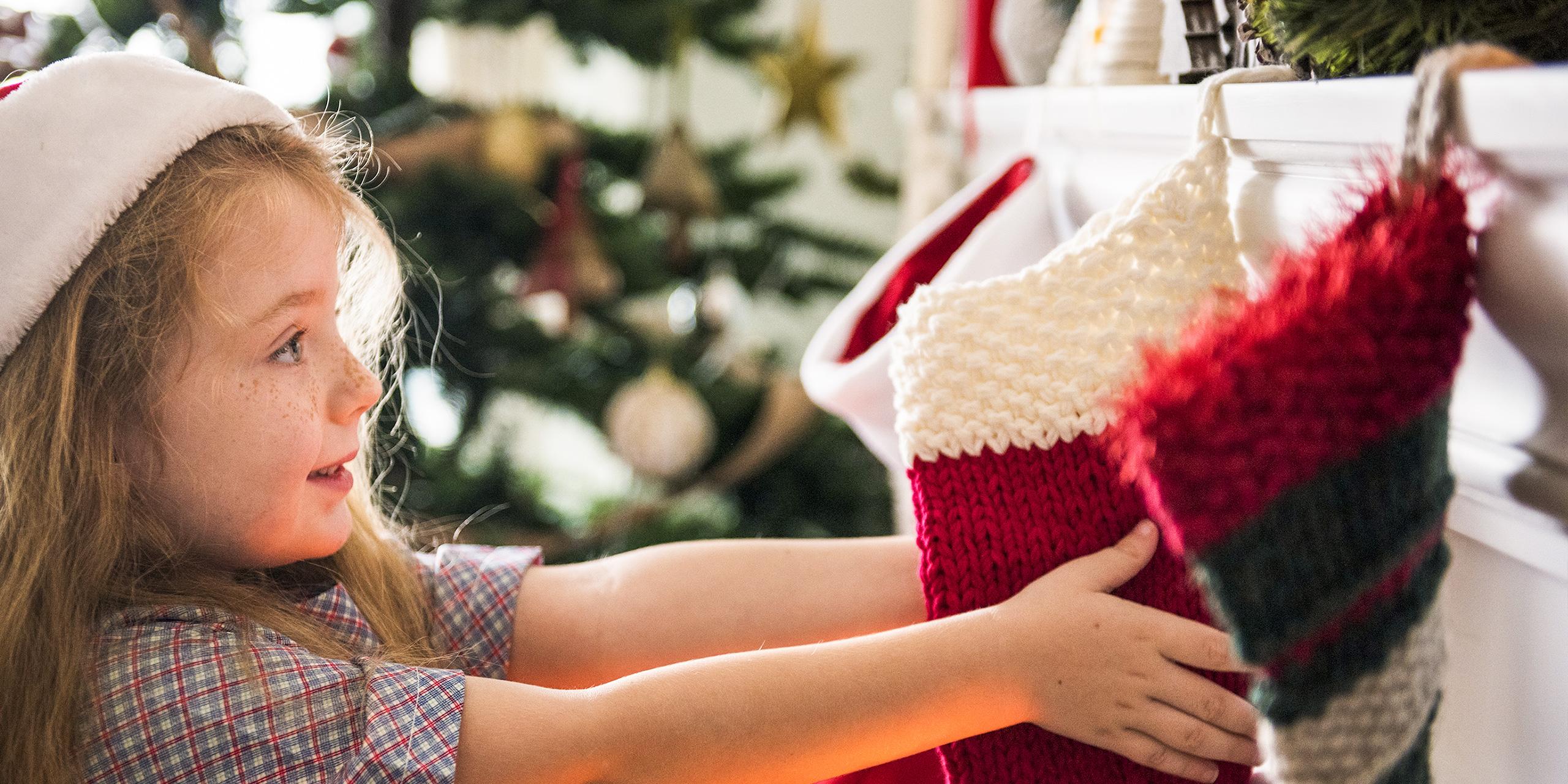 girl holding christmas stocking; Courtesy of Rawpixel/Shutterstock