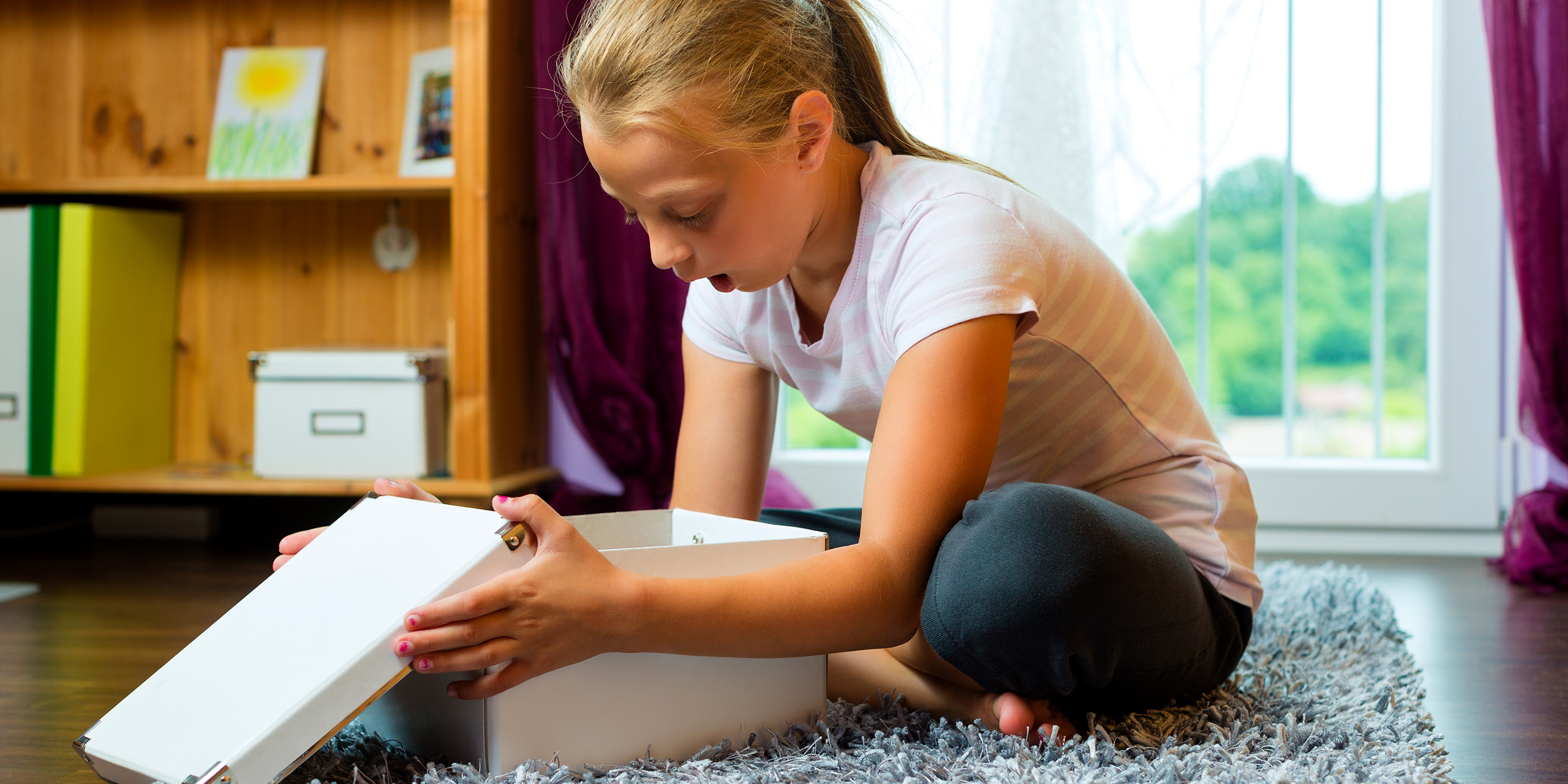 girl opening a box; Courtesy of Shutterstock