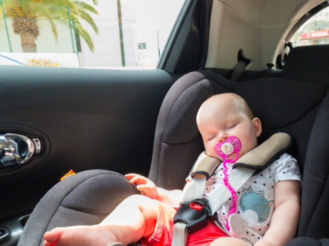 Cute baby girl is sleeping in the car on child safety seat; Courtesy of Patryk Kosmider/Shutterstock