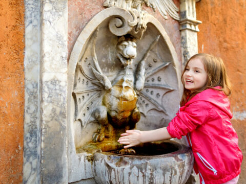 little girl playing with drinking water fountain in Rome, Italy; Courtesy of MNStudio/Shutterstock