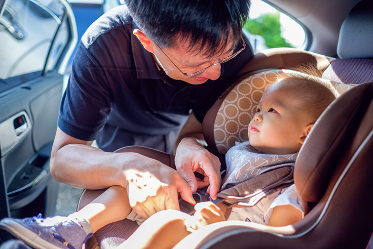 Smiling Middle age asian father helps his cute little asian 1 year old toddler baby boy child to fasten belt on car seat in car before driving; Courtesy of Yaoinlove/Shutterstock