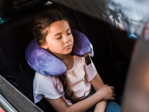 kid sleeping in car with neck pillow; Courtesy of LightField Studios/Shutterstock