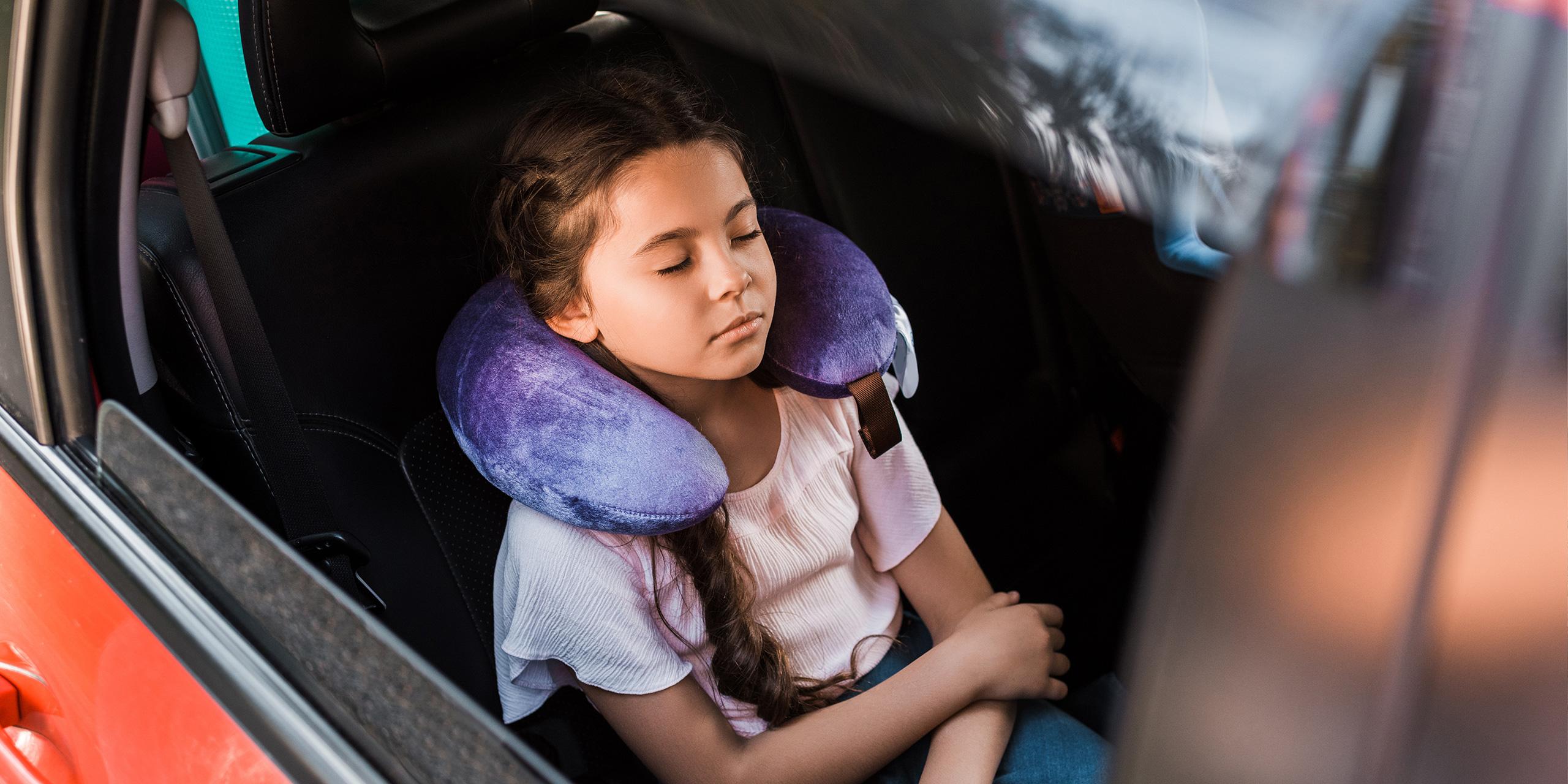 kid sleeping in car with neck pillow; Courtesy of LightField Studios/Shutterstock