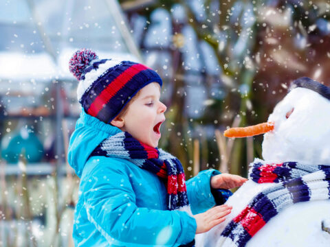 little kid boy making a snowman and eating carrot. child playing and having fun with snow on cold day.; Courtesy of Romrodphoto/Shutterstock