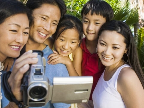Family Looking at Video Camera Screen; Courtesy of sirtravelalot/Shutterstock