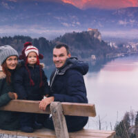 family posing for photo on lake bled in slovenia wearing weinter gear; Courtesy of Natalia Deriabina/Shutterstock