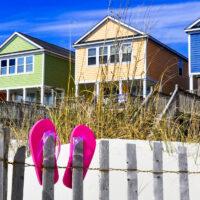Row of beach rentals on a summer day, pink flip flops on beach fence; Courtesy of StacieStauffSmith Photos/Shutterstock